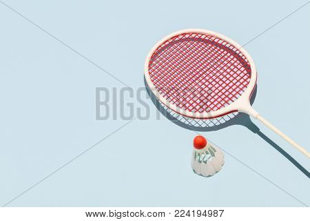 Oldschool badminton racket and birdie laying on a pastel blue background. Sports and leisure activities.