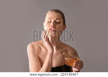 Beautiful young woman with honey on face against color background