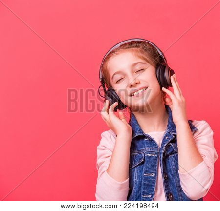 Beautiful teenage girl listening to music with earphones while her eyes closed, pink background