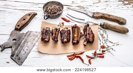 Grilled pork ribs on piece of brown paper with herbs, spices, butcher chopping knife and carving fork on white wooden table with cracked paint.