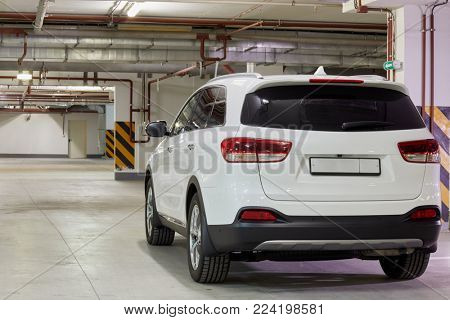 New white car at underground parking, rear view.