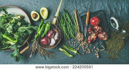 Winter vegetarian, vegan food cooking ingredients. Flat-lay of seasonal vegetables, fruit, beans, cereals, kitchen utencils, dried flowers, olive oil over grey linen table cloth background, top view
