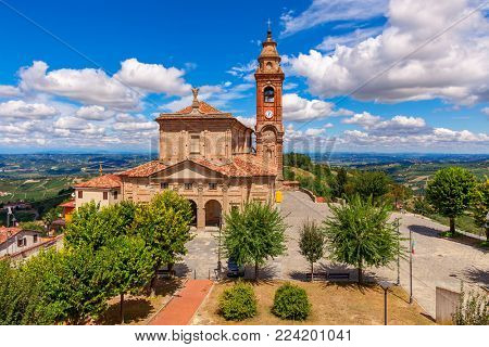 Old brick parish church under beautiful blue sky with white clouds in small town of Diano d'Alba in Piedmont, Northern Italy.