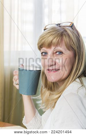 Cheerful elderly woman, drinking her morning coffee or tea at her home