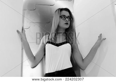 Black and white portrait of blond girl in hipster glasses, Beautiful blonde with glasses on a light background, black and white photo