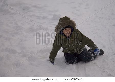 7 year old child, boy, in the snow laughing