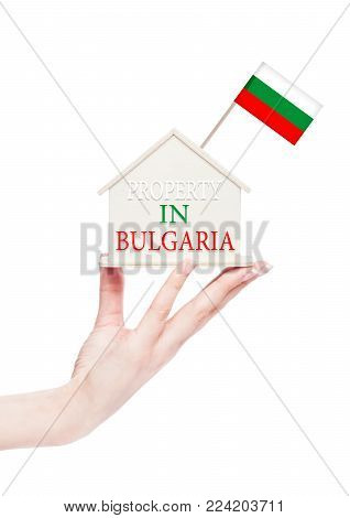 Female hand holding wooden house model with Bulgaria flag on top. Property in Bulgaria text