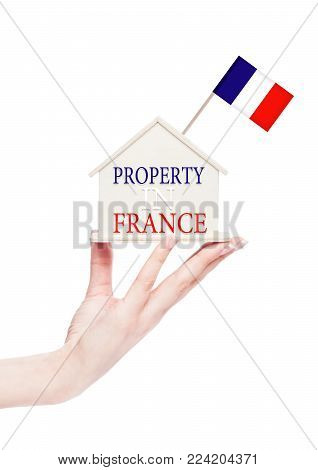 Female hand holding wooden house model with France flag on top. Property in France text