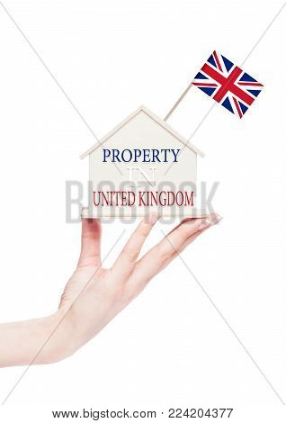 Female hand holding wooden house model with United Kingdom flag on top. Property inUnited Kingdom text