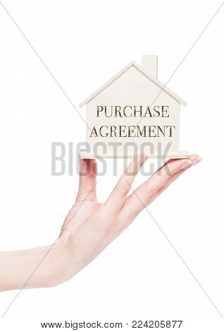 Female hand holding wooden house model with conceptual text. Purchase agreement