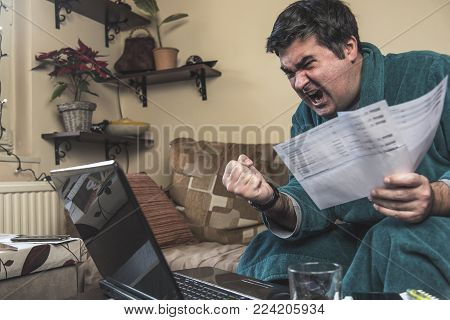 Enraged mature man yelling at his bills and financial reports, dressed in bathrobe, sitting in his living room poster