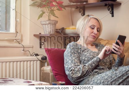 Mature blonde woman chatting with a friend or a relative over her cell phone, relaxing in her living room on a sofa