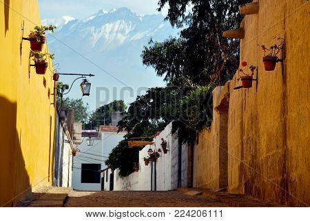 Colorful wall of an alleyway in the district of Yanauara in Arequipa, Peru and mountain Chachani in the background