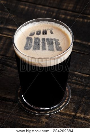 Glass of stout beer top with don't drive letters shape on wooden background