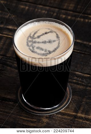Glass of stout beer top with basketball shape on wooden background