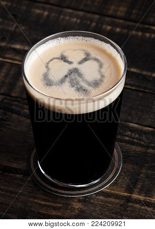 Glass of stout ale beer top with shamrock shape on wooden background