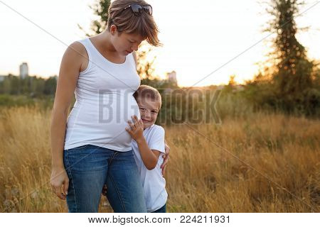 A pregnant mother hugs her son by the shoulders. A family portrait outside the city. Happy childhood and motherhood.