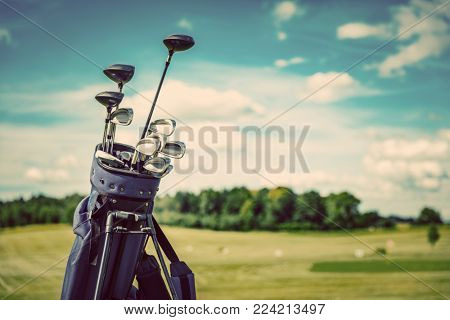 Golf equipment bag standing on a course. Summer sport and activity. Golf clubs close-up.