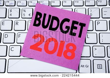 Handwriting Announcement text showing Budget 2018. Business concept for Household budgeting accounting planning written on sticky note paper on white keyboard background.