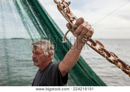 Commercial fisherman holding rusty chain, selective focus on weathered hand.