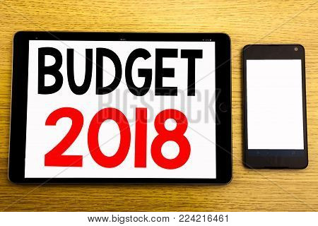 Writing text showing Budget 2018. Business concept for Household budgeting accounting planning Written on tablet, wooden background with sticky note and pen