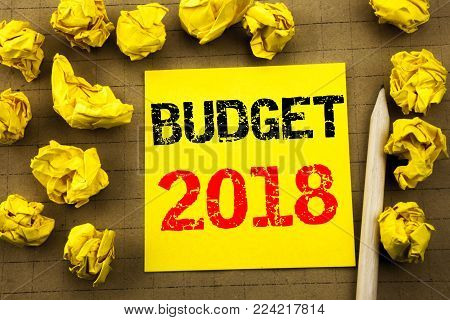 Handwriting text showing Budget 2018. Business concept for Household budgeting accounting planning written on sticky note paper on yellow vintage background. Folded yellow papers on the background