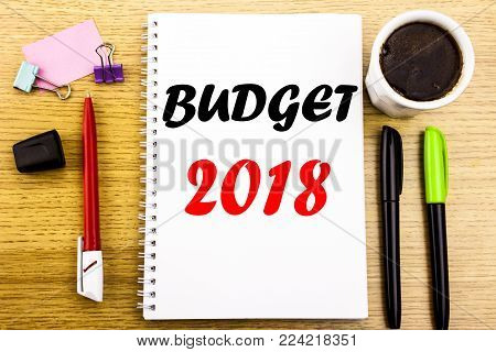 Hand writing text caption showing Budget 2018. Business concept for Household budgeting accounting planning Written on notepad paper background with space office view with pencil marker coffee