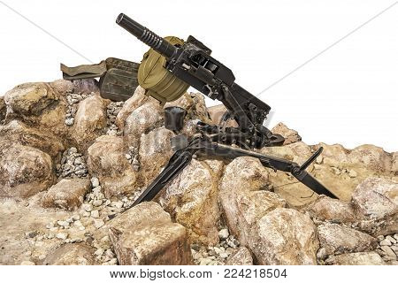 The image of a gun, standing on the stones. Drum magazine for cartridges. An armed clash in the desert or the mountains. For illustration and photo montage.