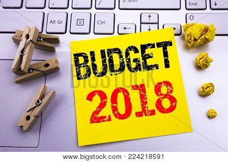 Hand writing text caption inspiration showing Budget 2018. Business concept for Household budgeting accounting planning written on sticky paper on the white keyboard background.