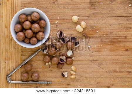 Shelling fresh macadamia nuts for eating or cooking in an overhead view of whole nuts, cracked shells and a nutcracker on a wooden bamboo board with copy space
