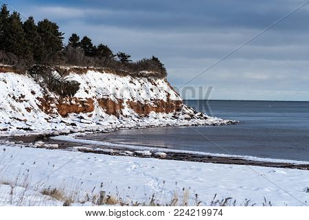 Snow on the sandstone cliffs along the shoreline of Prince Edward Island National Park, Canada.