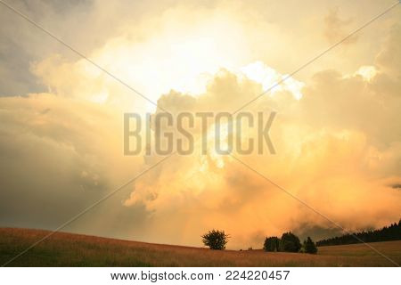 Dramatic sky with big clouds above Pasterka village in Table Mountain in Poland. Stormy weather, nat