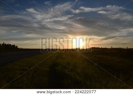 Sunset alongside a highway with big prairie skies
