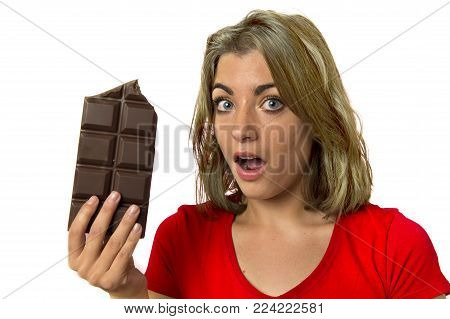 young pretty happy and excited girl holding big chocolate bar in sugar addiction temptation looking guilty skipping diet in unhealthy nutrition lifestyle and overweight concept isolated white background