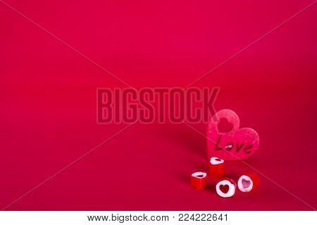 Red heart-shaped candy on a red background.