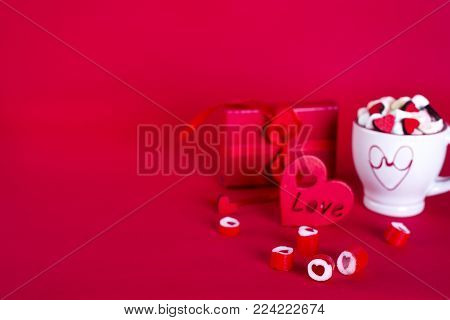 Red heart-shaped candy with tea of marshmallow and gift box on a red background.