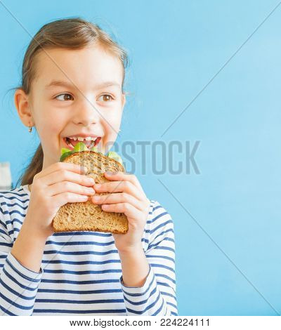 Smiling girl eating healthy sandwich with salad and avocados