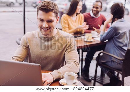 Web network. Attractive cheerful vigorous man sitting at cafe while looking at screen and smiling
