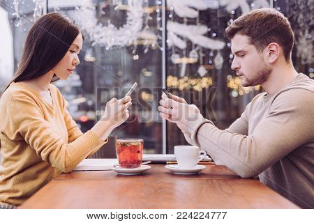 No real life. Attractive earnest pleasant couple sitting while holding phones and looking at the screens