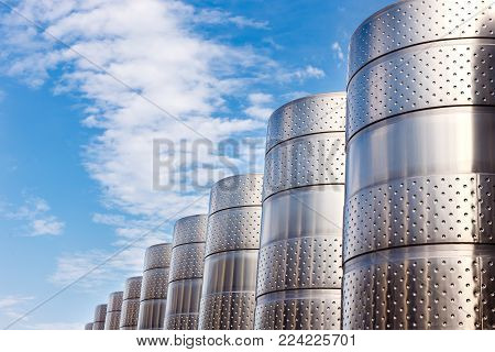 Modern technological industrial equipment of wine factory..Large stainless steel wine distilling vats on a blue sky background.