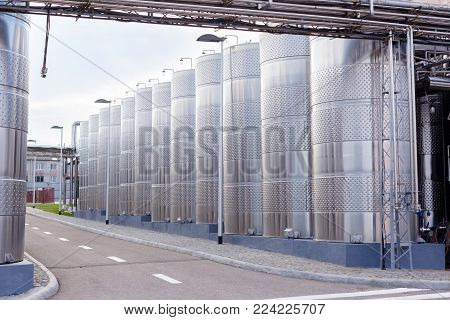 Modern technological industrial equipment of wine factory..Big stainless steel wine distilling tanks.