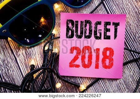 Hand writing text caption showing Budget 2018. Business concept for Household budgeting accounting planning written on the wood with sunglasses copy space