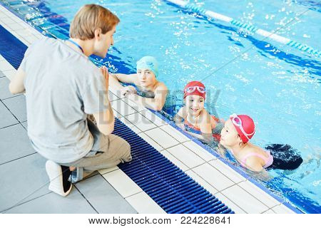 Swim trainer explaining his learners in swimming-pool what to do next