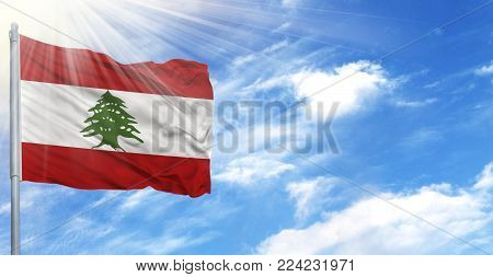 Flag of Lebanon on flagpole against the blue sky.