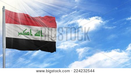 Flag of Iraq on flagpole against the blue sky.