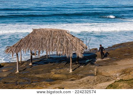 LA JOLLA, CALIFORNIA - JANUARY 27, 2018:  A surfer stretches near the iconic Windansea Beach surfer shack, a historical landmark built in 1998, and the home break location of many notable surfers in Southern California.