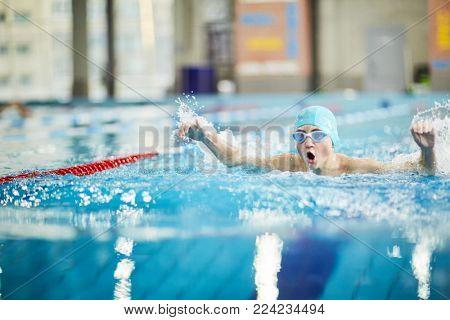 Professional swimmer splashing water while swimming energetically towards finish