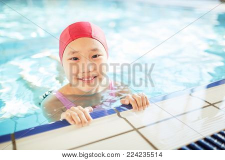 Cute little girl in swim-cap looking at camera during training in swimming-pool
