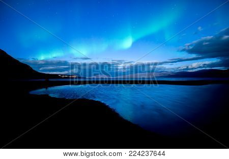 Northern lights dancing over calm lake in Sweden