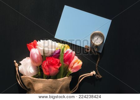Flowers and a pocket clock on a paper note - Colorful bouquet of diverse flowers in a jute bag, a vintage pocket watch and a blank blue message card, on a black background.